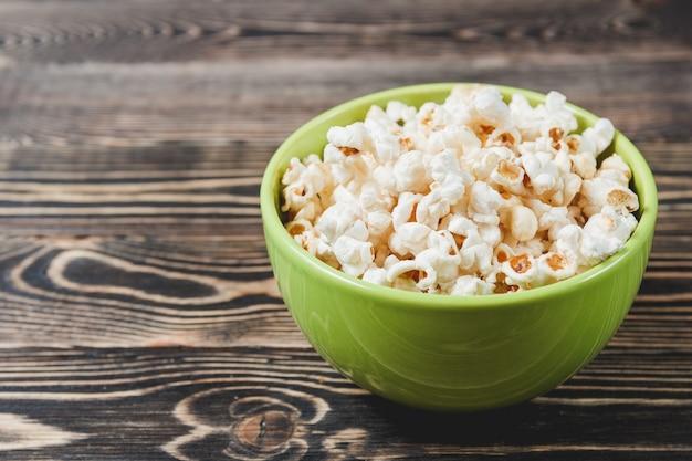 Süßes karamell-popcorn in der grünen schüssel auf hölzernem hintergrund