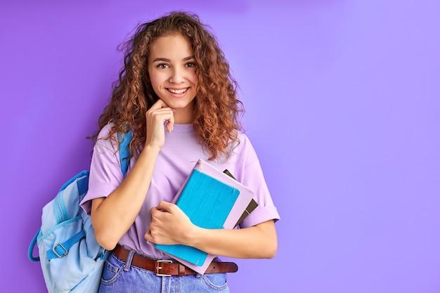 Süßes kaukasisches freundliches junges studentenmädchen, das bunte übungsbücher hält, bereit zu studieren