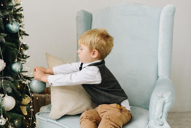 Süßes kaukasisches kleinkind, das in einem sessel sitzt und schönen weihnachtsbaum verziert