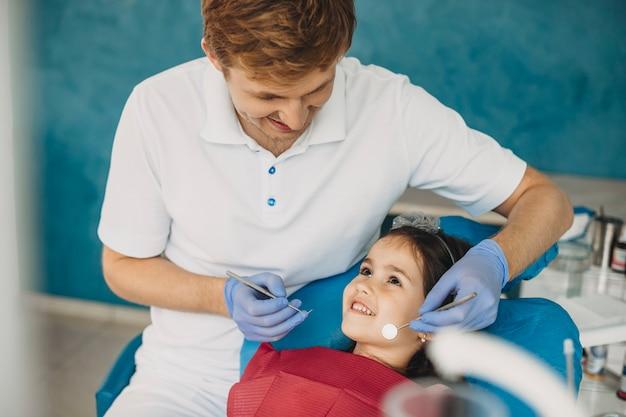 Süßes kind, das ihren arzt während der zahnuntersuchung ansieht. junger kinderzahnarzt, der lächelt, während er seinen kleinen patienten ansieht.