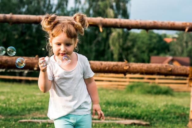 Süßes kind kind, das versucht, seifenblase zu fangen. sommer im dorf. warmer sonnenuntergang. glückliche kindheit.