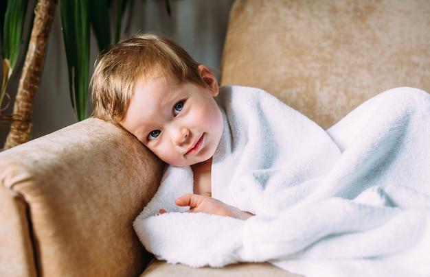 Süßes kind mit blauen augen in ein weißes handtuch gehüllt to
