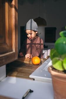 Süßes kind schält zitrusfrüchte am tisch in der küche