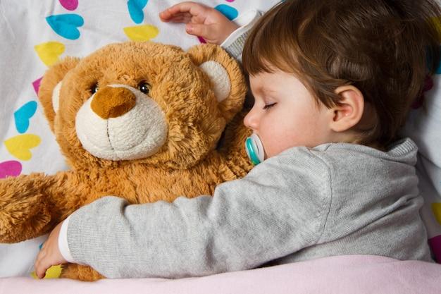 Süßes kind schläft mit teddybär