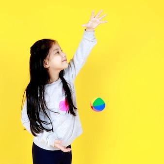 Süßes kleines asiatisches mädchen auf pullover lächeln, während sie kinderspielzeug spielen, indem sie die hand hoch über den kopf heben und den bunten ball loslassen, um ihn fallen zu lassen. kind freut sich, die schwerkraft zu lernen, indem es sieht, wie es herunterfällt