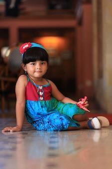 Süßes kleines asiatisches mädchen, das auf dem boden sitzt