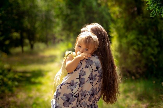 Süßes kleines baby im gelben kleid umarmt ihre mutter im grünen garten