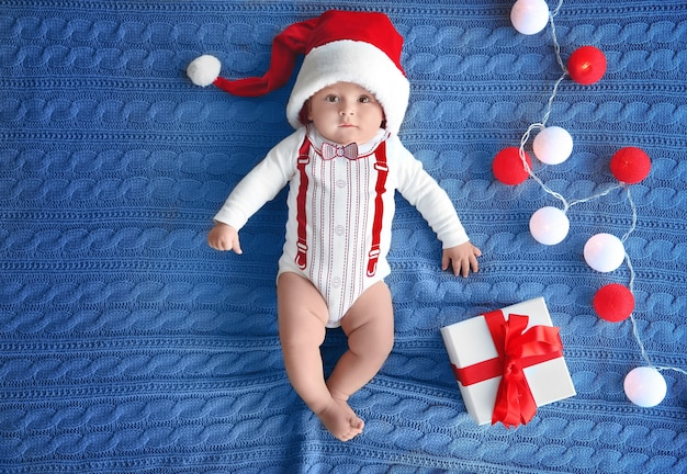 Süßes kleines baby in weihnachtsmütze mit geschenkbox und girlande auf strickstoff