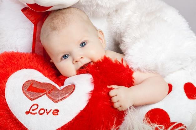 Süßes kleines baby umarmt das herz in den pfoten eines großen plüschbären