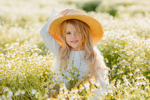 Süßes kleines blondes mädchen in einem baumwollkleid und strohhut geht in ein gänseblümchenfeld und sammelt sie im korb ein