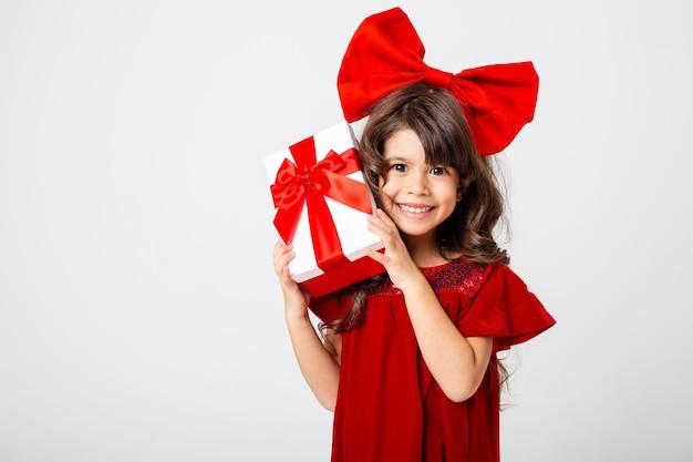Süßes kleines brünettes mädchen in einem roten kleid und mit roter schleife auf dem kopf hält eine geschenkbox in den händen