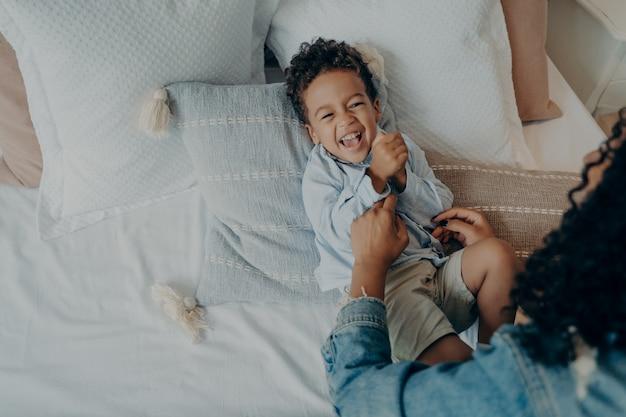 Süßes kleines jungenkind, das laut lacht und lächelt, während seine liebevolle mutter ihn mit vielen weichen kissen auf dem bett kitzelt, mutter erzählt ihrem sohn eine wirklich lustige geschichte, während sie glückliche zeit zusammen zu hause verbringt