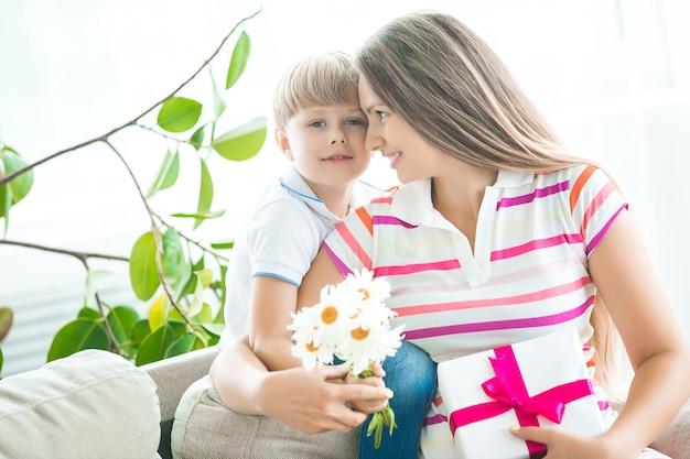Süßes kleines kind gratuliert seiner mutter zum muttertag