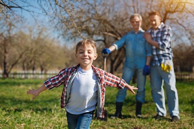 Süßes kleines kind mit ausgebreiteten händen, die in einem garten herumlaufen und sich über die zeit freuen, die mit seinem vater und opa verbracht wird