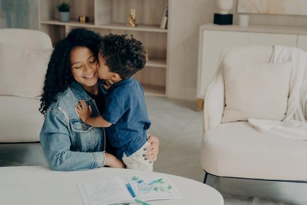 Süßes kleines kind mit lockigem haar, das seine lächelnde mutter sanft umarmt, die im wohnzimmer auf dem boden sitzt