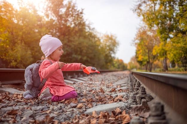 Süßes kleines kleinkindmädchen, das draußen hexenstein auf den verlassenen bahngleisen spielt.