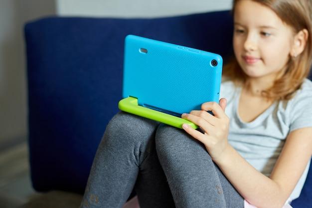 Süßes kleines mädchen, das auf der couch sitzt, technologiesüchtiges kind, das spaß daran hat, online-spiele auf einem digitalen tablet-computer zu spielen, anwendungen zu verwenden, informationen zum surfen im internet zu hause zu nutzen,