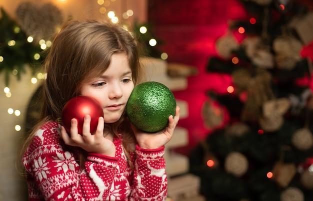 Süßes kleines mädchen mit weihnachtsdekoration durch den weihnachtsbaum, der kugeln hält.