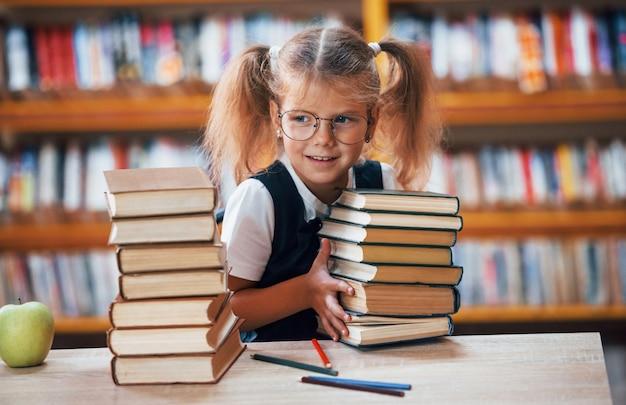 Süßes kleines mädchen mit zöpfen ist in der bibliothek