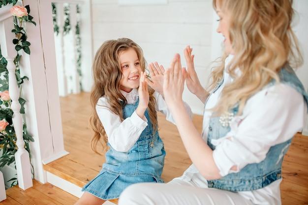 Süßes kleines mädchen spielt einen kuchen mit ihrer mutter, familie hat spaß am morgen, lächelnde vorschultochter mit mutter klatscht in die hände, genießt freizeit