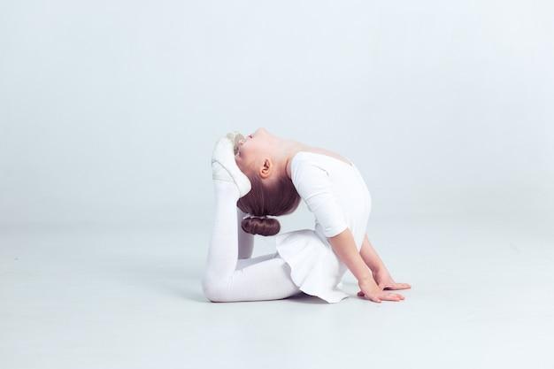 Süßes kleines mädchen träumt davon, eine ballerina zu werden kindermädchen in einer weißen tanzkleidung tanzt