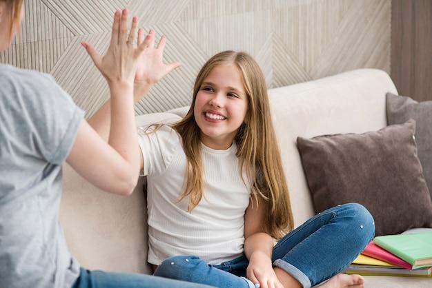 Süßes kleines mädchen und ihre mutter geben high five, während sie hausaufgaben machen