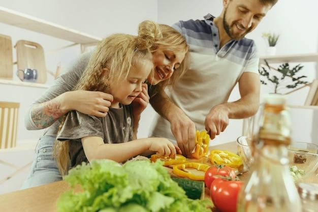 Süßes kleines mädchen und ihre schönen eltern schneiden gemüse in der küche zu hause