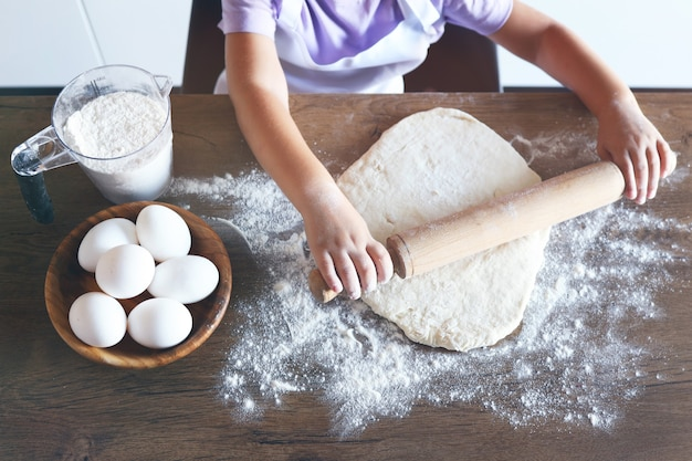Süßes kleines süßes mädchen lernt, wie man einen kuchen macht, in der heimischen küche, familienkonzept, vintage-farbton. ansicht von oben