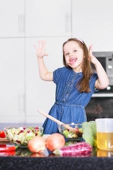 Süßes kleines süßes mädchen verwöhnt sich in der modernen küche des hauses, familienkonzept