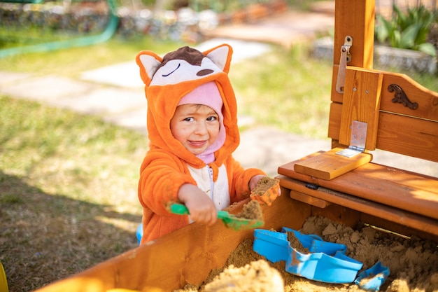 Süßes kleinkind im orangefarbenen overall spielt an einem sonnigen tag im sand im sandkasten im freien
