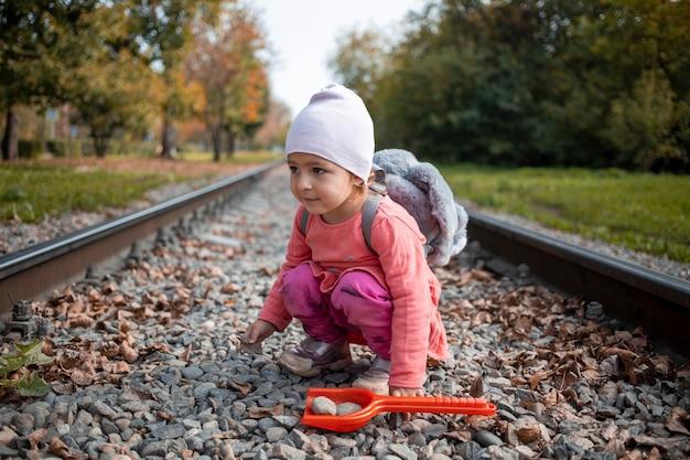 Süßes kleinkind spielt allein auf den bahngleisen