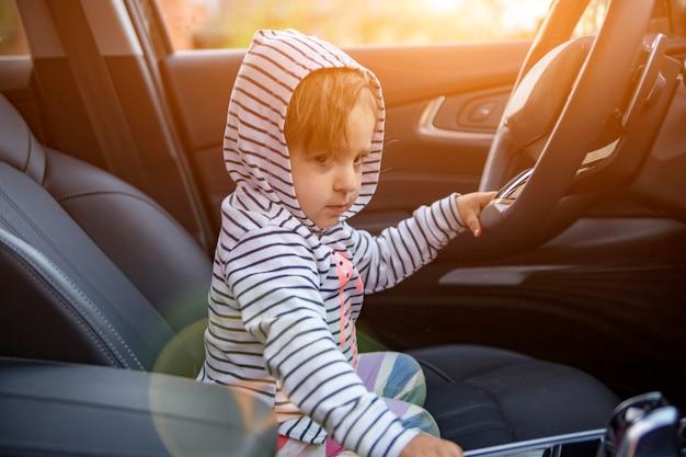 Süßes kleinkind spielt fahrer im modernen auto der eltern. entzückendes kind erforschen die fahrer des premium-autos. babyfahrer, junger fahrer hält lenkrad im auto