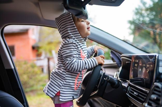 Süßes kleinkindmädchen, das ein modernes auto fährt.