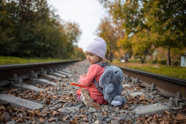 Süßes kleinkindmädchen spielt an einem sonnigen sommertag allein auf der eisenbahn, gefährliche situation.