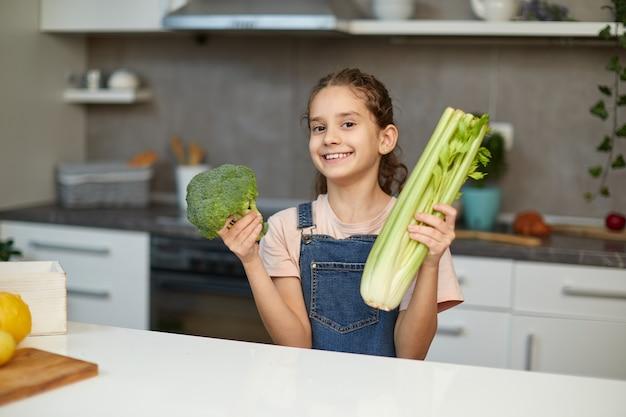 Süßes lachendes und lockiges kleines mädchen steht in der nähe des tisches in der küche und hält grünes gemüse in den händen.