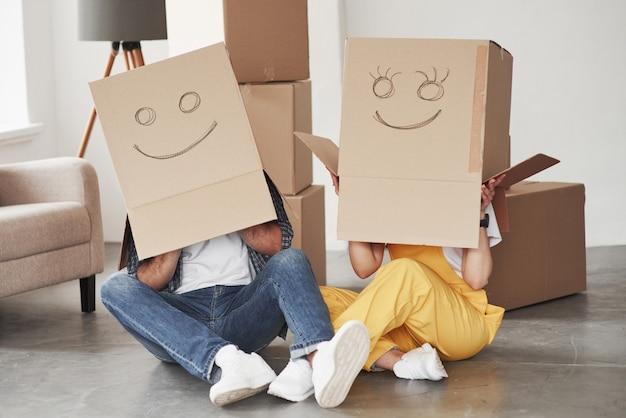 Süßes lächeln auf kisten, die auf den köpfen sind. glückliches paar zusammen in ihrem neuen haus. konzeption des umzugs