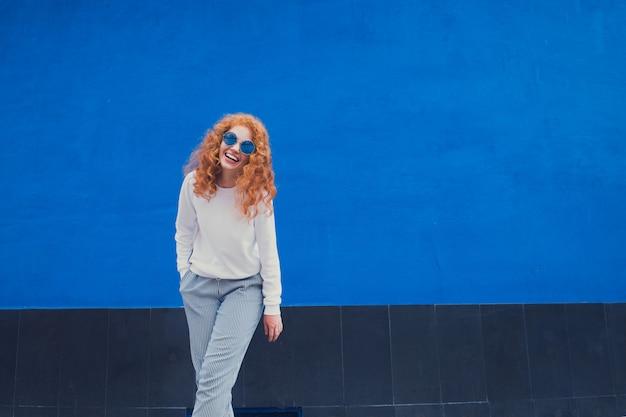 Süßes lächelndes mädchen in der sonnenbrille, die auf blauem hintergrund lächelt