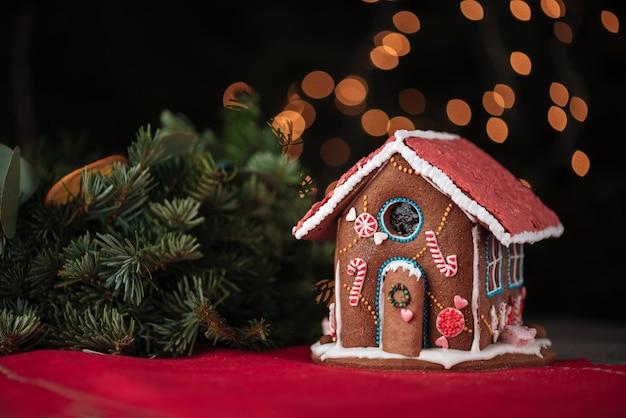 Süßes lebkuchenhaus und weihnachtsbaumast über funkelnder wand