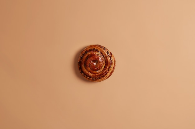 Süßes leckeres frisch gebackenes wirbelndes zimtbrötchen für ihren snack oder ihr frühstück. appetitlicher ungesunder blätterteigkuchen auf beigem hintergrund. süßwaren- und bäckereikonzept. ganze leckere französische rolle