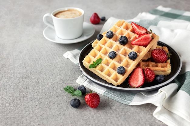 Süßes leckeres frühstück mit waffelteller, erdbeere und blaubeere, minzblatt und tasse kaffee auf konkretem grauem hintergrund. foto in hoher qualität