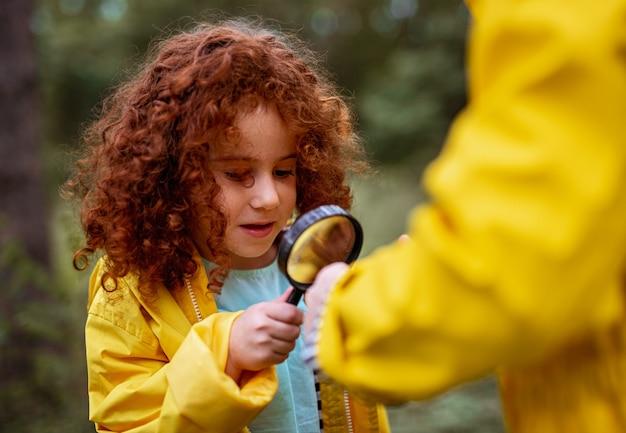 Süßes, lockiges kleines ingwermädchen im gelben regenmantel, das durch die lupe schaut, während es die umgebung mit nicht erkennbaren geschwistern im sommerwald erkundet