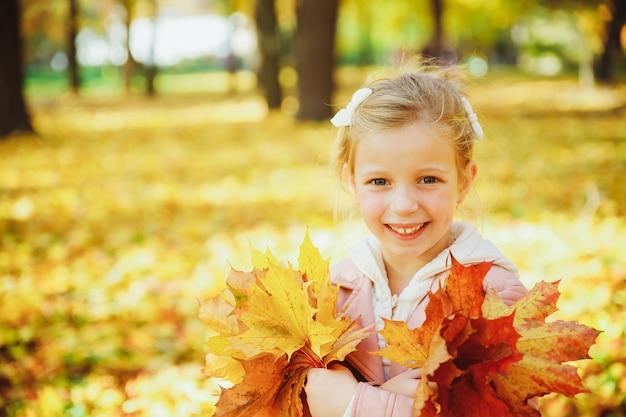 Süßes lockiges mädchen. das kleine lustige mädchen, das mit gelb spielt, verlässt im wald. kind auf einem spaziergang im herbstpark. goldener herbst. kleinkindmädchen mit herbstlaub