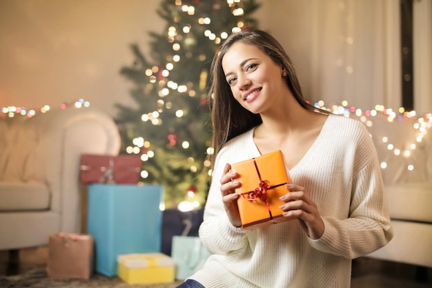 Süßes mädchen, das im wohnzimmer, ein weihnachtsgeschenk halten sitzt