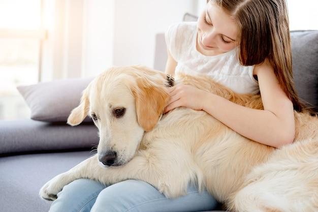 Süßes mädchen, das niedlichen hund hält, der auf sofa drinnen sitzt