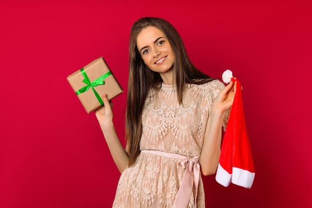 Süßes mädchen hält eine geschenkbox und ein weihnachtsmannhutfoto auf einem rosa hintergrund