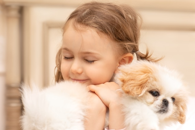 Süßes mädchen hält und umarmt flauschigen welpen tierpflege freundschaft umarmt starke emotionale petrenthood