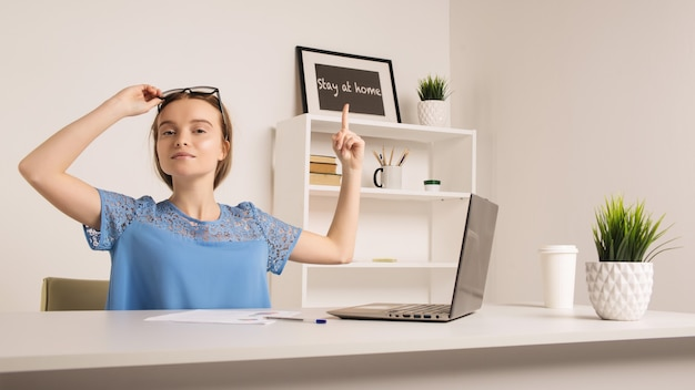 Süßes mädchen im büro zeigt einen finger auf die inschrift zu hause bleiben.