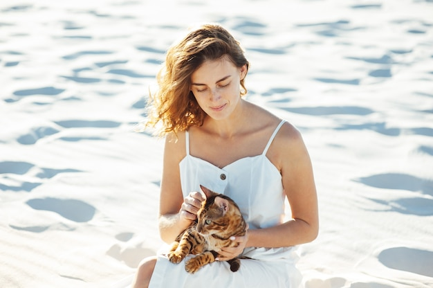 Süßes mädchen im weißen kleid am strand umarmt ihre bengalkatze