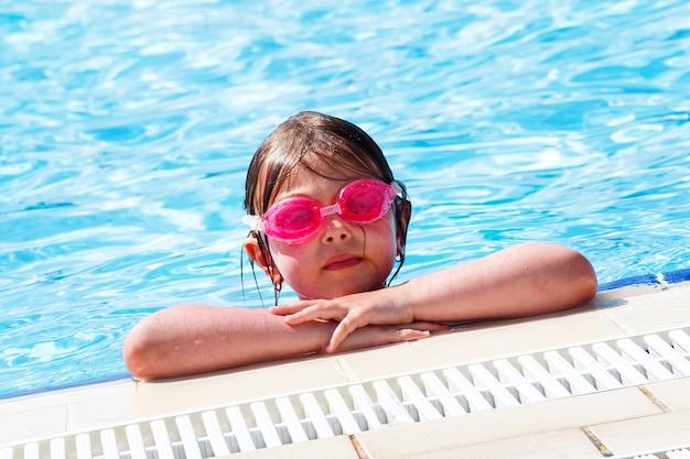 Süßes mädchen in rosa wasserbrille, das im pool schwimmt und sucht