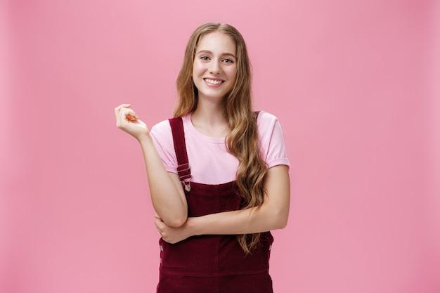 Süßes mädchen in trendigen overalls mit langer, gewellter frisur und leichtem make-up, das in lässiger pose steht und ...